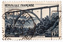 An old blue french postage stamp with an image of Garabit Viaduct railway bridge. Leeds, England - April 20 2018: an old blue french postage stamp with an image royalty free stock photos