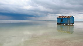 Old blue house abandoned in the middle of the salt lake during an approaching storm. Salar Baskunchak stock video footage