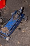 Old blue hydraulic floor jack or car jack on the floor.  royalty free stock photos