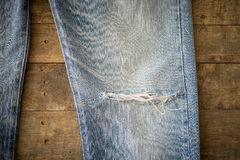 Old blue jeans with torn on wood background Royalty Free Stock Image