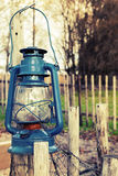 Old blue kerosene lamp hangs on wooden outdoor fence. Vintage toned photo with filter effect stock photo