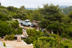 Old blue land rover pickup standing near small house in the forest in mountains on the island in mediterranean sea Stock Photo