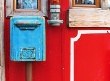 Old blue mailbox hanging on red wall Stock Image