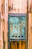 Old blue mailbox with rust and a hole and dirty mail on a wooden wall Royalty Free Stock Image