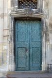 Old blue metal forged door in a stone building Royalty Free Stock Photo