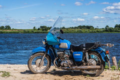 Old blue motorbike. Stand near the Oka river Royalty Free Stock Photo