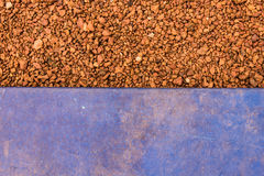 Old blue plastic on brown pebble in back Stock Images