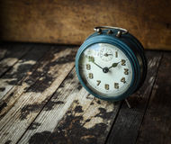 Old blue retro analog alarm clock on dark wooden background Stock Image