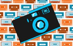 Old blue retro vintage antique hipster obsolete camera with a lens and a diaphragm on the background of a pattern of multi-colored. Audio cassettes. Vector Stock Photography