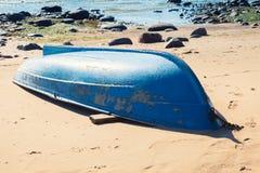 Old blue rowboat lays on sandy beach Stock Photos