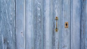 Old blue run-down wooden door and lock Stock Photos