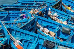 Old blue rusty boats in Essaouira port stock photography