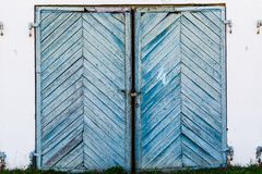 Old, blue, skewed garage doors on a collapsing brick wall stock images