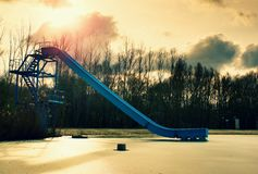 Old blue sliding track on lake beach, frozen watel level. Winter time Stock Images