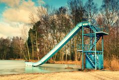 Old blue sliding track on lake beach, frozen watel level. Winter time Royalty Free Stock Images