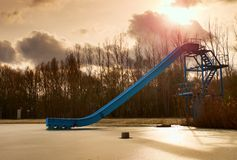 Old blue sliding track on lake beach, frozen watel level. Winter time Royalty Free Stock Image