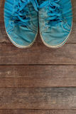Old blue sneakers. On a background of wood Royalty Free Stock Photos