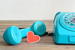 Old blue telephone and heart  shaped tag Stock Photos