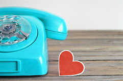 Old blue telephone and heart  shaped tag Royalty Free Stock Image