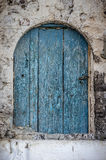 Old blue timber door in the scuffed wall Stock Photography