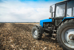 Old blue tractor in a empty field. Agricultural machinery, field work. Stock Photography