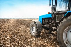 Old blue tractor in a empty field. Agricultural machinery, field work. Royalty Free Stock Image
