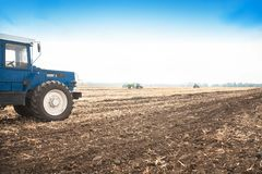 Old blue tractor in a empty field. Agricultural machinery, field work. Stock Photo