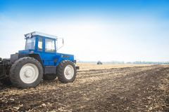 Old blue tractor in a empty field. Agricultural machinery, field work. Stock Photos