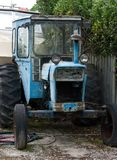 An old blue tractor full of rust parked somewhere in the South Island in New Zealand royalty free stock image