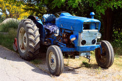Old blue tractor on the road Stock Image