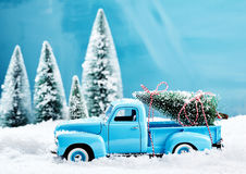 Old blue vintage toy truck with Christmas tree. Old blue vintage toy truck with a Christmas tree loaded on the back driving through thick snow in a winter forest stock image