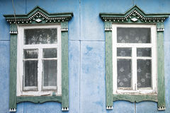 Old blue wall with two windows. Two old wooden windows on the blue cracked wall Royalty Free Stock Images