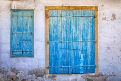 Old blue weathered door and window in Cyprus stock photography