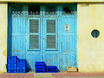 Blue Door, Stone Walls Blue Crates & Old Newspapers. Drinks crates and a bundle of newspapers outside of a small shop in Malta. The old weather beaten blue Stock Photo