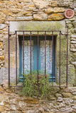 Old blue window closed and covered by rusty metal jail on a rock wall Royalty Free Stock Image