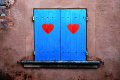 Old blue window shutters with red hearts Royalty Free Stock Images