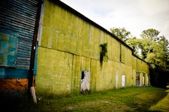 Old Blue Wooden Building and Green Metal Building Background stock images