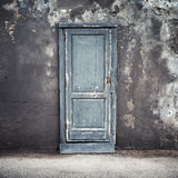 Old blue wooden door in concrete wall Stock Photos