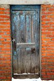 Old blue wooden door. An old blue obsolete locked wooden door. Brick building Royalty Free Stock Images
