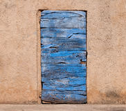 Old blue wooden door and orange wall in Roussillon in France Stock Image
