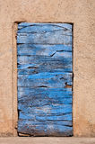 Old blue wooden door and orange wall in Roussillon in France Royalty Free Stock Image