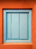 A old blue wooden door or shutter in an orange wall Stock Images