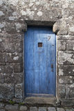 Old blue wooden door in a stone wall. In Locronan Royalty Free Stock Photo