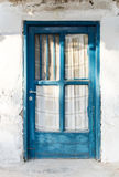 Old blue wooden door on a white wall Royalty Free Stock Photo