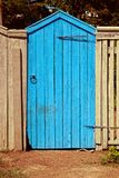 Old blue wooden gate and gray fence Royalty Free Stock Photo