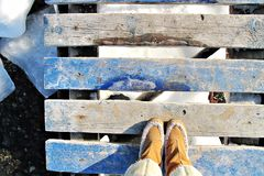 Old blue wooden pier and winter boots stock images