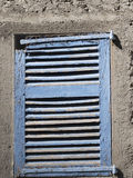 Old blue wooden window on white wall spoiled by atmospheric agen. Ts Royalty Free Stock Image