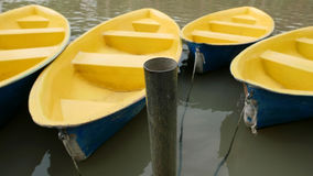 Old blue and yellow recreation boat on lake Royalty Free Stock Image
