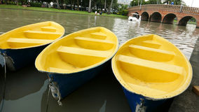 Old blue and yellow recreation boat on lake Stock Image