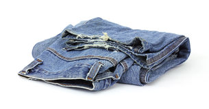 Old bluejeans. A pair of old bluejeans which are fraying on the bottom on a white background royalty free stock photo